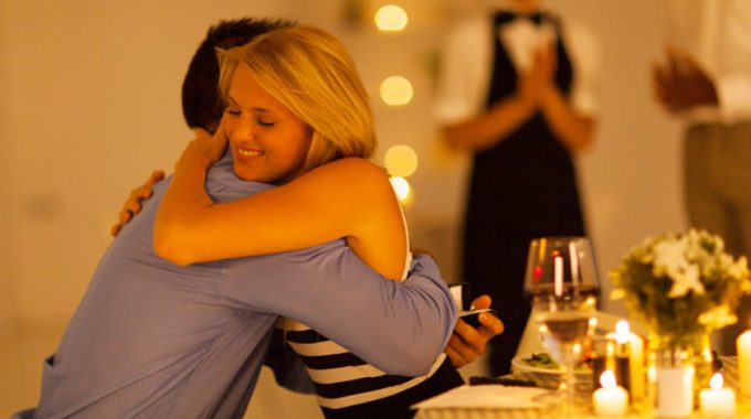 Woman Hugging Boyfriend At A Romantic Dinner For Two
